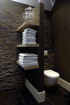 Floating shelves on a partition wall for the toilet. If you have the little bit of space, this is a neat idea! (I also love the rough look of the stacked stones for a feature wall! Bathroom Toilets, Bathroom Renos, Laundry In Bathroom, Bathroom Storage, Bathroom Interior, Modern Bathroom, Master Bathroom, Bathroom Ideas, Bathroom Shelves