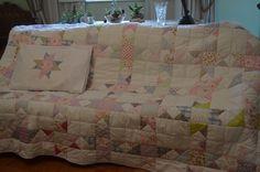 Colcha em patchwork. <br>Mede 1,72m da largura x 2,40m de comprimento. <br>Pespontada à mão. <br>Toda confeccionada em tecidos de algodão. <br>Inclui fronha medindo 50cm x 68cm. <br>Verso em tecido branco de algodão.