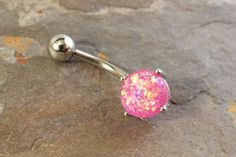 """Synthetic pink fire opal belly button jewelry ring. The 8mm pink opal is prong set and glow in the light with radiant iridescence. The opal belly ring is 14 gauge and 3/8"""" long (10mm), and is made of"""