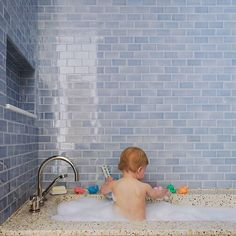 Our hearts fluttered at the sight of this sweet painterly photo over on marthastewart.com. A precious little one bathing in bubbles against a #backsplash of soft #blue #tiles! This kids' #bath is designed to grow in style with the children who use it; the blue of the #tile isn't overly cutesy and the #terrazzo tub will stand the test of time. We encourage you to find the full photo gallery & source info at http://iren.es/kidtile. / #tiletuesday #bathroom #bathroomdesign #walltile #bluetiles…