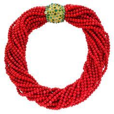 René Boivin coral Torsade with Gold and Emerald Clasp, with 27 strands of deep red coral beads, measuring approximately 38cm in length when twisted; 55cm when laid straight, clasp measuring 3.2cm x 3.5cm, circa 1960.
