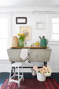 In the mudroom, a glossy black floor provides a break from the all-white surface throughout the house. Lovingly weathered salvaged pieces, like the concrete sink and chippy old frames, add soul to an all-white space.