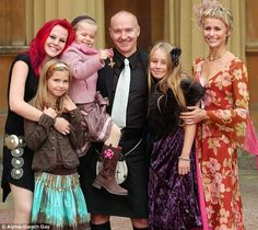 Support: Midge collecting his OBE in 2005, with his daughters (from left) Molly, Ruby, Flossie, Kitty and wife Sheridan