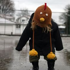 Puddle Jumper: a little tot wearing a knit earflap chicken hat with tassels