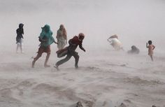 People walk through a hail storm near the Ravi river in Lahore, Pakistan