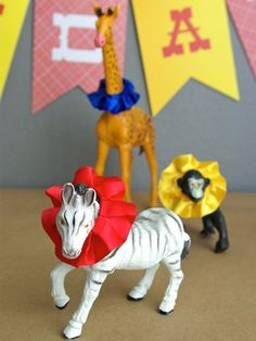 Circus Themed Party: totally been collecting animals to do this, but I was just going to run crepe paper streamers through my sewing machine to gather them for the ruffles. And I'm going to add tiny party hats. Small circle cut in half, folded into a cone, and hot glue a tiny pom pom to the tip. Happiness!
