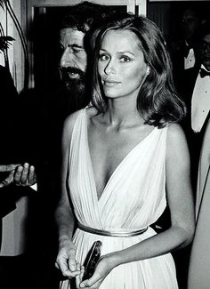 lauren hutton timeless in a Grecian white deep v neck gown with sleek belt and gently wavy hair