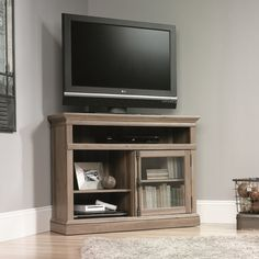Featuring a salt oak finish and glass door cabinet, this essential wood stand adds contemporary appeal to your parlor or den ensemble. Top it with your sleek flat-screen, then use the built-in shelves to stow DVDs and accessories.
