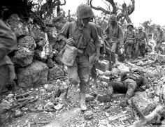 US Marines pass a dead Japanese soldier in a destroyed village, Okinawa. April 1945.