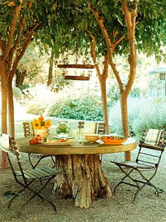 Tree stump serves as base for a rustic garden table - I really love this idea from Interiorholic! (And I have a similar table my great-grandmother made for the house)