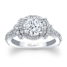 This unique white gold diamond halo engagement ring features a prong set round diamond center, encircled with diamonds and embellished with shared prong set diamonds cascading down the dainty shank for a look of sheer elegance.<br /> <br /> Also available in rose, yellow gold, 18k and Platinum.