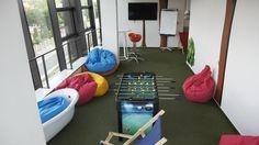 """Sala odbiega od biurowych standardów: piłkarzyki, owalna akrylowa wanna, leżaki plażowe, kolorowe stoliki, hamaki, siedziska """"worki"""" oraz trawa zamiast wykładziny."""