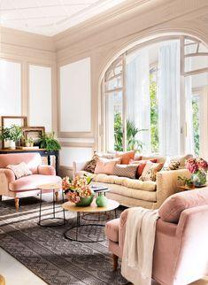 salón-con-butacas-de-terciopelo-rosa-y-sofá-ocre-sobre-alfombra-gris-y-mesitas-auxiliares-redondas 464791