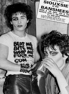 [That b/w Banshees/Adam Ant concert poster again, Siouxsie boredly drinking a Coke while Adam Ant stands around in t-shirt printed with shoc...