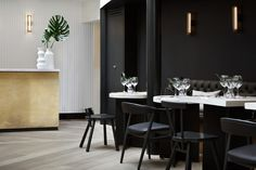 Black walls of the restaurant area contrasting to the white oak and weathered brass bar - My Hotels Group Chelsea boutique hotel designed by Design Haus Liberty. Luxury boutique hotel located in the heart of Chelsea inspired by the the local area. Designs feature on the Martyn White Designs blog.