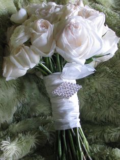 white O'Hara garden roses and white ranunculus, finished with hand tied ribbon and brooch
