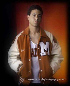 High school senior wearing letter jacket with orange color background.