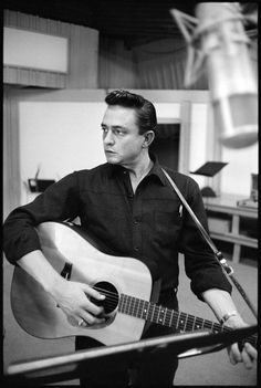 Young Johnny Cash strumming his acoustic guitar. His style, stance, and the overall method of playing guitar was incredibly impressive, sort of commanding, one might say!