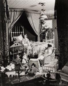 Young girl photographed on Christmas Morning with a vast array of toys, child seated in bed.åÊ