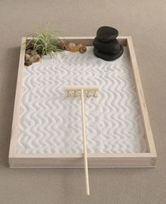 Zen gardens are miniature landscapes and often inspire meditation and contemplation. This Zen garden is inspired by the Yin Yang and has two imbedded succulents.