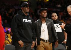 """Recording artist Sean """"Diddy"""" Combs, left, and boxer Floyd Mayweather Jr., right, watch warmups before the Los Angeles Lakers play against the Los Angeles Clippers in an NBA basketball game in Los Angeles, Tuesday, Oct. 29, 2013. (AP Photo/Danny Moloshok)"""