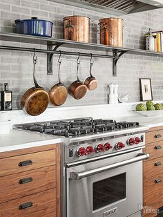 Homeowners skipped upper cabinets in favor of one long custom shelf. The steel storage unit holds cookware close to the pro-style range. Copper pots and pans add warm reflective shine to the space.
