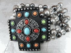 Iron Cross Bracelet decorated with colorful stone dots    Stretches with four strands of burnished silver and clear beads    Nickle and Lead safe    Designed in the USA