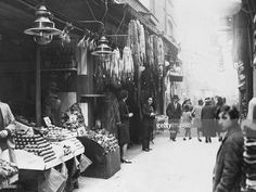 Berwick street market in Soho, London, with stalls selling fruit and vegetables and fur coats and stoles c.1930.