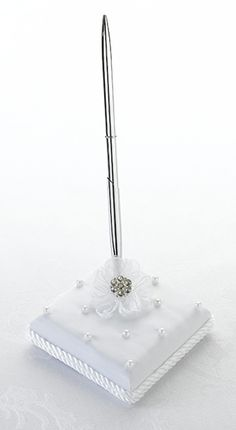 "Lillian Rose Pearl and Flower Pen Set This pen set includes a silver pen with black ink and a 3.25"" x 3.25"" white satin pen base. The base is decorated with scattered white pearls and a white flower with rhinestone ornament. A matching guest book is sold separately. Price $15.00"