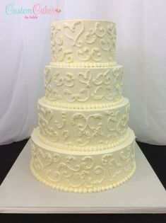 ivory wedding cake with scrollwork and hearts