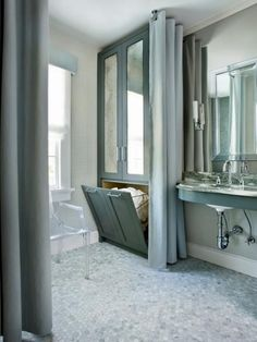"""When renovating a bath in a historic home, designer Mark Williams had to work within a small footprint. """"Baths were not as luxuriously proportioned back then so we had to get creative with storage solutions,"""" he says. """"We built in a large piece — designed to look like an armoire — but is actually linen storage above, and a hamper below. The antiqued mirror insets in the upper cabinet doors make the whole space feel larger."""""""