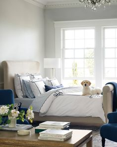 This neutral bedroom has a sophisticated feel with its sleigh bed, glass chandelier, blue armchairs, and glass lamp. Neutral Bedding, Linen Bedding, Bedding Sets, Bed Linens, Design Furniture, Bedroom Furniture, Bedroom Decor, Design Bedroom, Magazine Design