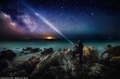 A man shines a torch but his light his overshadowed by the stars above Circeo National Par...