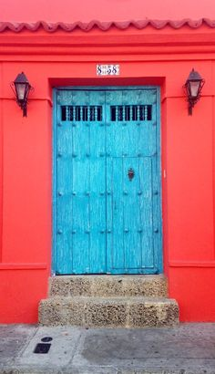 I love the combination of the bright blue double doors with the bold red of the walls! Combined, they make this doorway really dramatic and inviting and set high hopes for the rest of the house. BR x