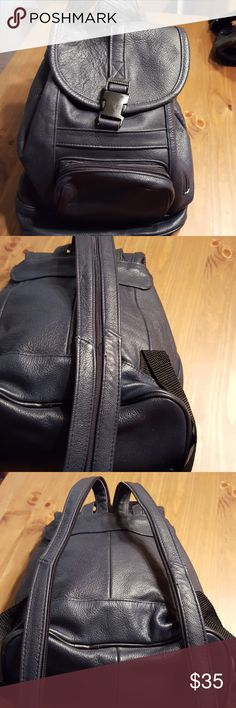 Navy Leather Backpack Purse Adjustable This is in awesome condition and is 100% leather. The length is approx 14 in. The bottom is approx 10 by 5. The large compartment is accessible by a snap closure and tie cinch. There are 2 outer zippered compartments. The adjustable strap can zip or unzip to use as either a backpack or slung over the shoulder. There's also a loop for hanging. It comes from a smoke-free environment. The only flaw is a small tear in the fabric at the zipper in the…