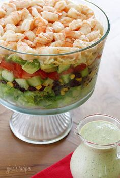 A beautifully layered salad with shrimp, avocados, grilled corn, black bean salsa, cucumbers, tomatoes and cheese. I served this with creamy cilantro tomatillo dressing.  Because there is no cooking involved, this makes a perfect summer potluck dish and the presentation is beautiful. One of my facebook fans mentioned she always brings a trifle dish to a party and gives the host the dish as a gift, cute idea! If you don't have a trifle dish, you could always layer this in a large platter i...