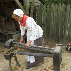 """FARM: A historical interpreter """"breaks"""" flax, a step in the process of transforming raw flax into fiber that can be used to make thread."""
