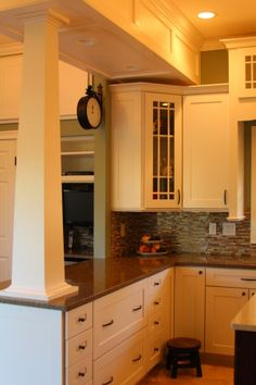 Welcomed Warmth, Kitchen remodel with white craftsman style cabinets and pantry, brushed bronze hardware, quartz countertops, and stainless steel appliances. French door refrigerator, rangetop cooktop with telescopic downdraft vent, convection microwave and oven, hot/cold water on demand, seperate drink refrigerator, eat-in area with additional seating at the peninsula. Full coat closet with extra storage above., Corner display cabinet and pillar.      , Kitchens Design