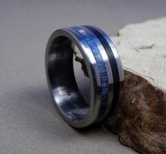 This titanium ring is one of our hand milled and sized handmade rings that weve inlaid with two narrow strips of wood; ebony and blue box elder. We