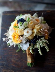 White lilac, yellow and pale orange roses, dusty miller, navy berries.