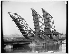 Tower bridges, Fort Point Channel, Boston, Mass.  They no longer exist but this is an example of three side by side rolling bascule lift bridges.  This counter weighted bridge rolls back on a track to lift its roadway or railroad track.