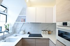 A combination of white colour scheme & uplighting on the cabinets creates an inviting kitchen and gives the illusion of space