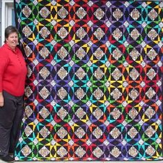 """The quilter said, """"I am a Storm-at-Sea pattern freak and this layout of  """"Rainbow-After-the-Storm"""" design has become my favorite!  I'm pictured next to the custom-made quilt for my dear friend, Eric.  After the quilt was completed, Eric wanted to know how many colors  I used in the quilt ~ which I thought was an odd question, until he  informed me that he was color-blind."""""""