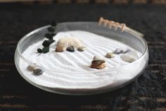 Mini Zen garden for stress relief at your desk. A shallow bowl, some sand, a few cool pebbles and trinkets, and a mini rake made from coffee stirrers.