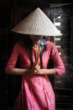 A Vietnamese lady in Hoi An prays with sticks of incense, wearing traditional Vietnamese clothing.