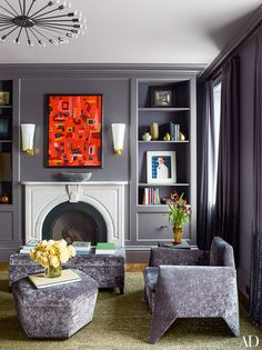 An artwork by one of the homeowners adds a burst of color above the master bedroom's fireplace, while a Matthew Barney photograph is displayed on a bookshelf; the armchairs (one is shown) and small ottoman are vintage designs by Lloyd Wright.