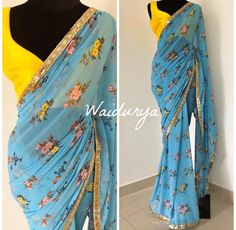 Butter soft georgette sari in a sky blue with beautiful peach and yellow floral motifs all over. The border is a textured sequin one in a dull gold. The blouse fabric is a canary yellow raw silk. Such a vibrant way to walk in to summer! Trendy Sarees, Stylish Sarees, Fancy Sarees, Sari Blouse Designs, Saree Blouse Patterns, Chiffon Saree, Georgette Sarees, Sky Blue Saree, Yellow Saree