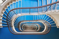 the series explores budapest's spiral staircases, revealing patterns that pull your gaze towards the center.