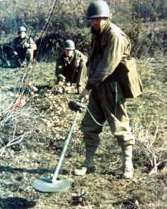 Italy - US Army Engineers, trying to locate land mines by using a magnetic detector and by probing with a bayonet.