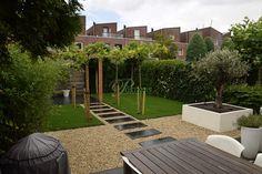 Tweede gedeelte van deze tuin opgeknapt met een pergola van douglas, grind, gras en tegels! En perfect aangekleed met mooie kunststof bloembakken...
